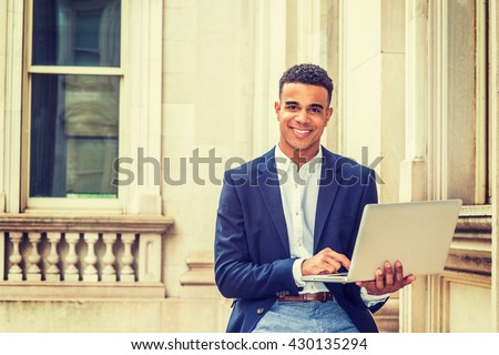 African American college student studying in New York, wearing black blazer, sitting inside vintage office building on campus, reading, working on laptop computer, smiling. Instagram filtered effect.