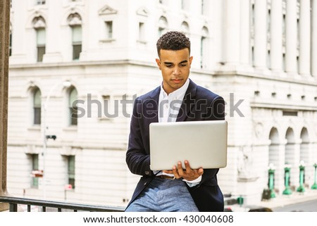 African American college student studying in New York, wearing black blazer, sitting on railing by vintage office building on campus, reading, working on laptop computer. Instagram filtered effect.