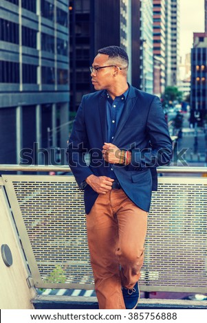 African American college student studying in New York, wearing blue jacket, brown pants, glasses, bracelets, standing on balcony, holding fists in front, looking away, sad, thinking, lost in thought. - stock photo