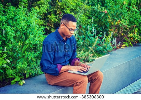 African American college student studying in New York, wearing blue shirt, brown pants, bracelets, glasses, sitting by green plants on campus, looking down, typing, working on laptop computer.   - stock photo