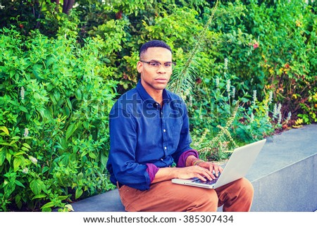 African American college student studying in New York, wearing blue shirt, brown pants, bracelets, glasses, sitting by green plants on campus, typing, thinking, working on laptop computer.   - stock photo