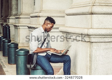 African American College Student studying in New York. Wearing gray shirt, jeans, carrying shoulder leather bag, a black man sitting on metal pillar on street, reading, working on laptop computer.  - stock photo