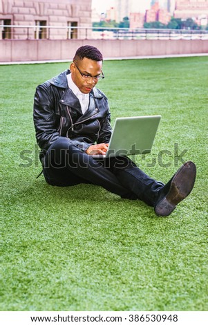 African American college student studying in New York. Wearing leather jacket, jeans, leather shoes, glasses, a young black man sitting on green lawn on campus, reading, working on laptop computer.  - stock photo