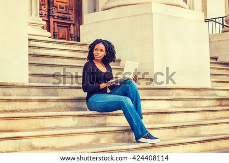 African American college student studying in New York. Wearing long sleeves, V neck top, jeans, leather sneakers, a black girl sitting on stairs outside office on campus, working on laptop computer.  - stock photo