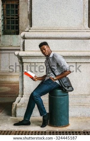 African American College Student studying on street in New York, wearing gray shirt, jeans, cloth shoes, wristwatch, carrying shoulder leather bag, listening music with earphone, reading red book.