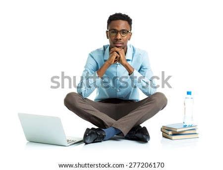 African american college student with laptop, books and bottle of water sitting on white background - stock photo