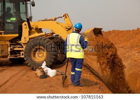 African American construction site worker wearing blue overalls and yellow high visibility safety jacket standing and watching bucket digger digging trench on sandy rocky land