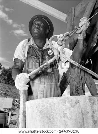 African American construction worker at the Douglas Dam on the French Broad River, one of the Tennessee Valley Authority public works projects of the New Deal. June 1942. - stock photo