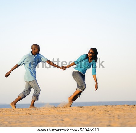 African American couple hand in hand on the beach - stock photo