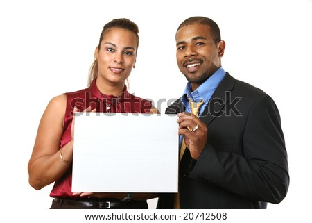 African American couple in business attire holding small white blank sign in front of them. Isolated on white. - stock photo