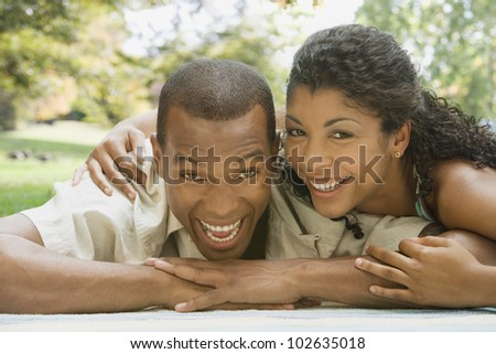 African American couple laying on blanket - stock photo