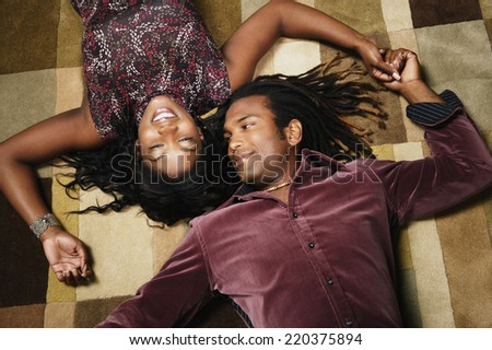 African American couple laying on floor holding hands - stock photo