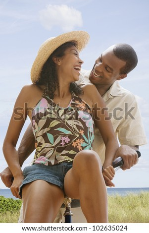African American couple on bicycle at beach - stock photo