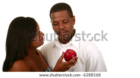 african american couple posing as adam and eve. eve offering apple to adam