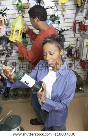 African American couple selecting birdhouse in shop - stock photo