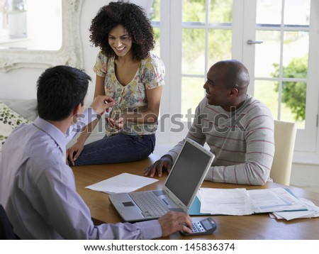 African American couple sitting at table with financial advisor - stock photo