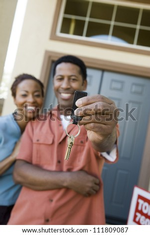 African American couple standing in front of a new home