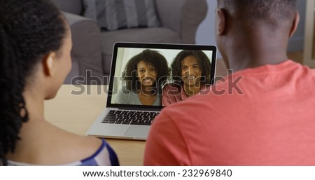 African American couple talking to family over video chat on laptop - stock photo