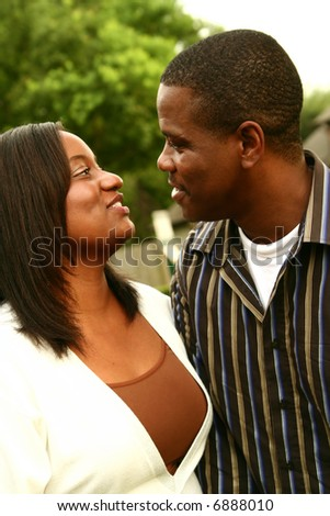 african american couple talking while walking with tree background