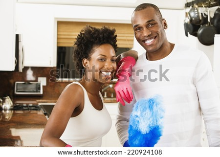 African American couple with cleaning tools - stock photo
