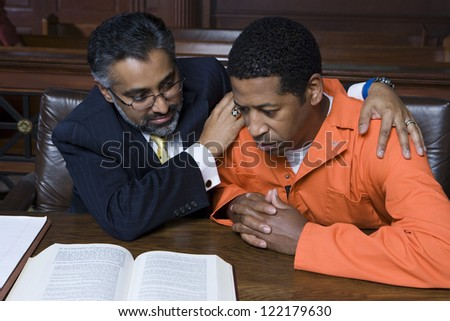 African American criminal sitting with advocate in courtroom - stock photo
