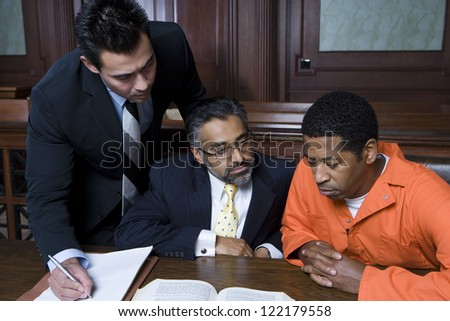 African American criminal sitting with two advocates in courtroom - stock photo