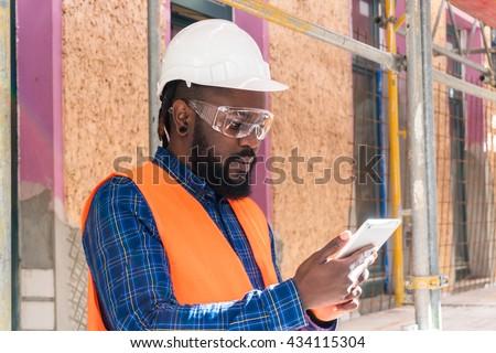 African american engineer wearing safety equipment (glasses, helmet and jacket) checking documents on tablet computer at construction site - stock photo