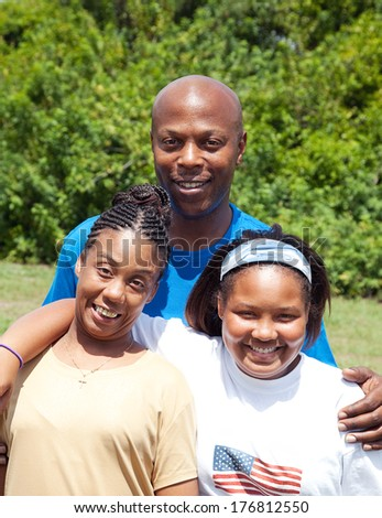 African-american family consisting of father, mother, and adolescent daughter.  Mother has cerebral-palsy.   - stock photo
