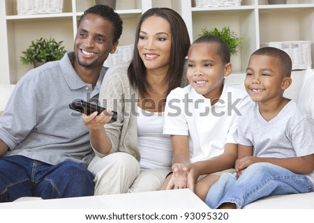 African American family, mother & father parents and two sons, having fun watching television together using the remote control - stock photo
