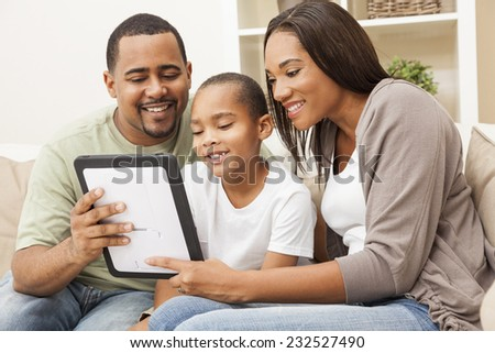 African American family, parents and son, having fun using tablet computer together - stock photo