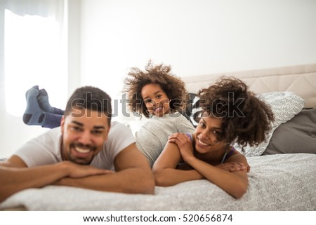 African american family relaxing together in bed.