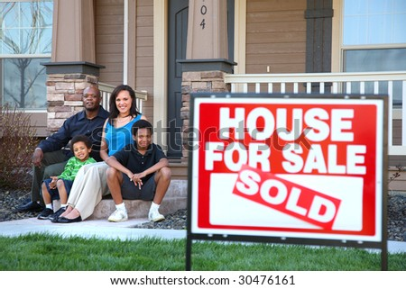 African American family sitting together on front steps of home with real estate sign in foreground