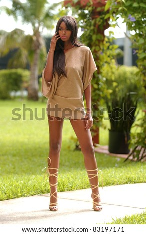 African American fashion model with sexy long legs in short dress standing with tropical trees on background - stock photo