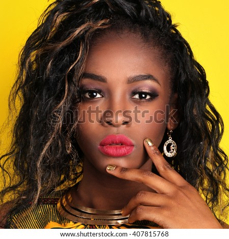 African-american fashion style. Beautiful African woman wearing color dress and bijou looking at camera while standing against yellow background. Latin woman with makeup, nail polish and hairstyle. - stock photo