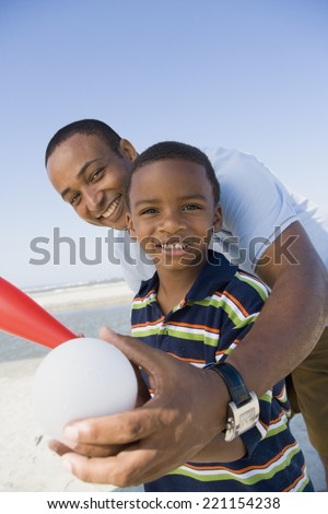 African American father and son holding baseball - stock photo
