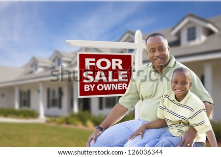 African American Father and Son In Front of For Sale By Owner Real Estate Sign and House. - stock photo