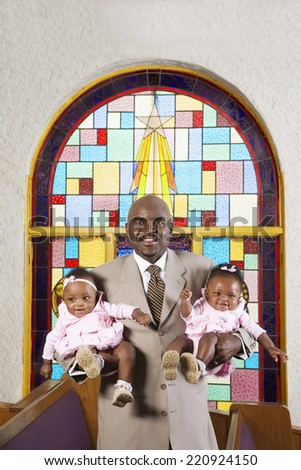 African American father holding babies in church - stock photo