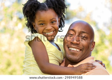 African American Father holding his daughter - stock photo