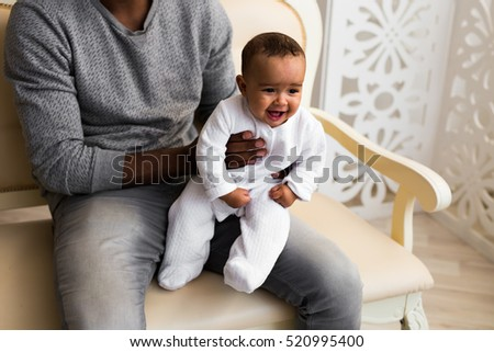 African American Father Playing With Mixed Race Baby Son At Home
