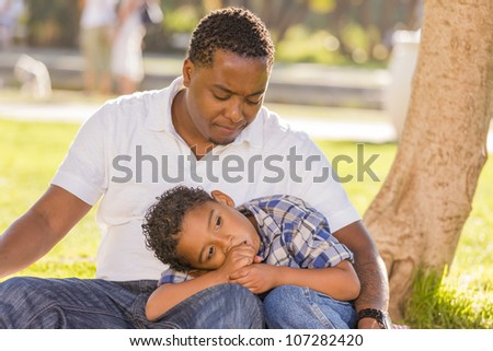 African American Father Worried About His Mixed Race Son as They Sit in the Park. - stock photo