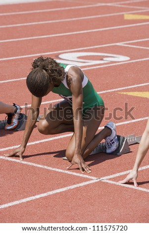 African American Female athlete with competitors at starting line - stock photo