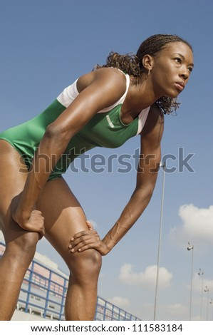 African American female athlete with hands on knees - stock photo
