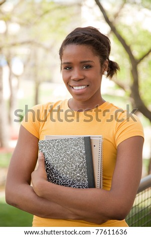 African American Female College Student outdoors with books