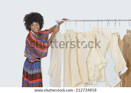 African American female designer with sewing patterns on clothes rack over gray background - stock photo