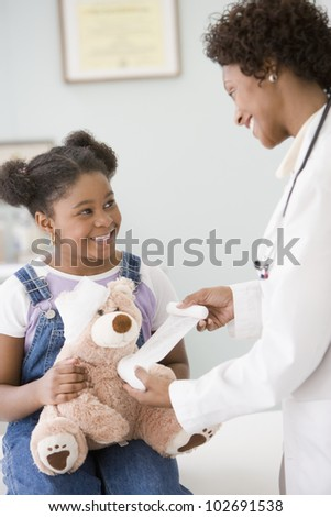 African American female doctor bandaging girl's teddy bear - stock photo
