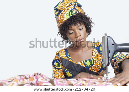 African American female fashion designer sewing fabric over gray background - stock photo