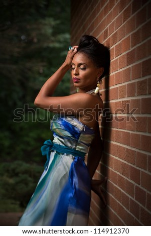 African American Female Fashion Model Portrait Low Key Outdoor Eye Closed Posing Wearing Colorful Dress - stock photo