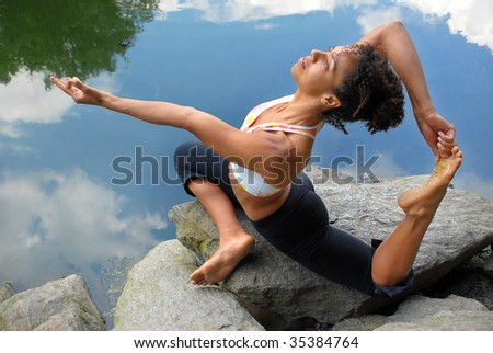 african american female in king pigeon yoga pose - stock photo