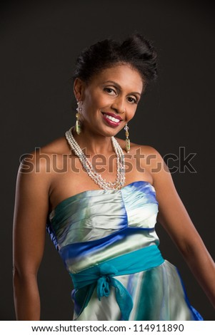 African American Female Model Portrait Low Key on Grey Background Wearing Colorful Dress - stock photo