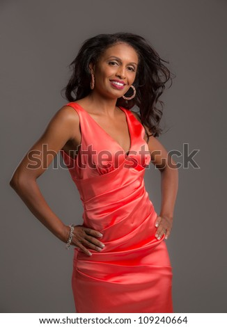 African American Female Model Portrait Low Key on Grey Background Wearing Red Dress - stock photo